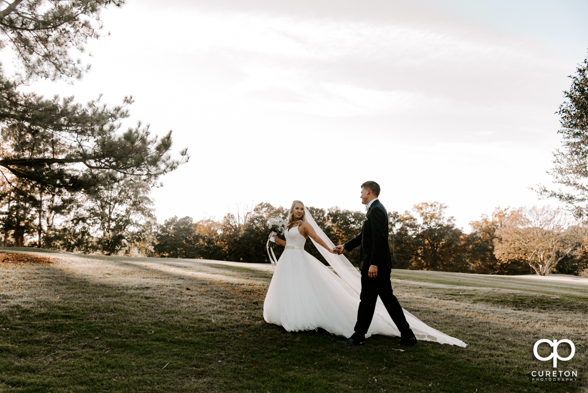 Bride and groom walking on the golf course after their wedding ceremony.