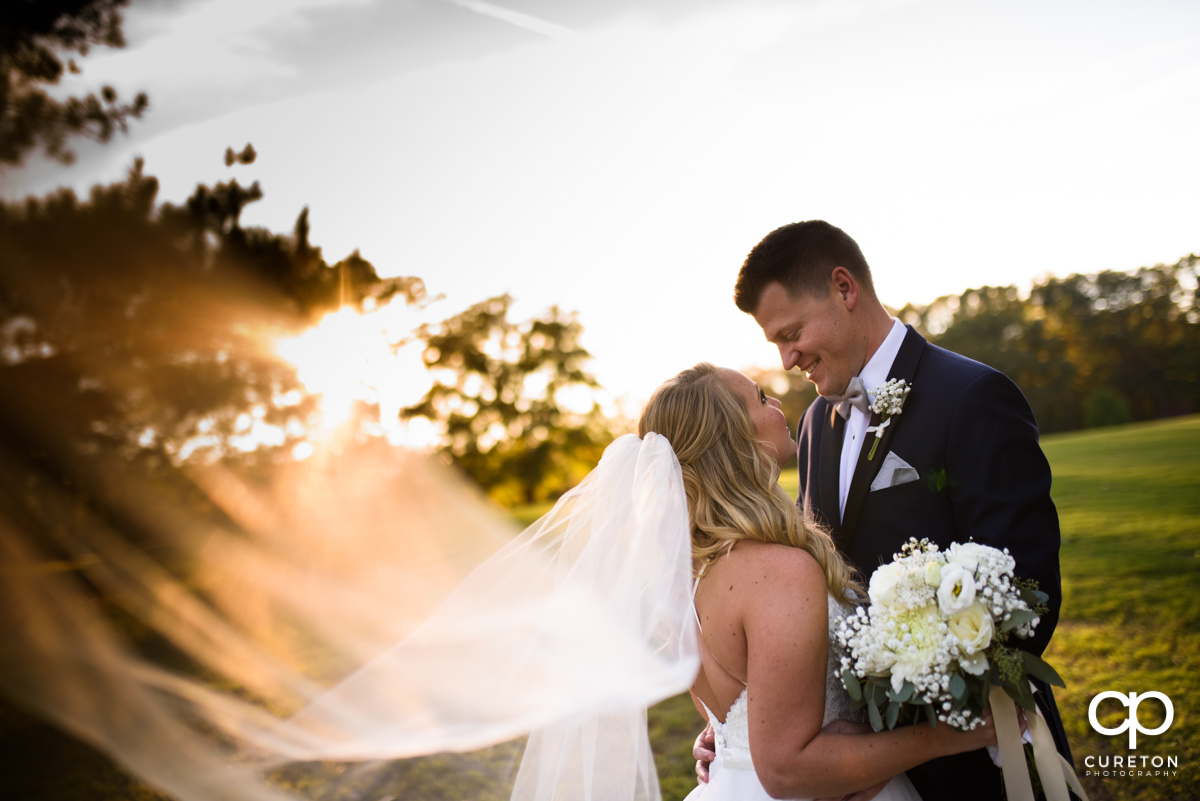 Groom and bride hugging during golden hour as her veil blows in the wind.
