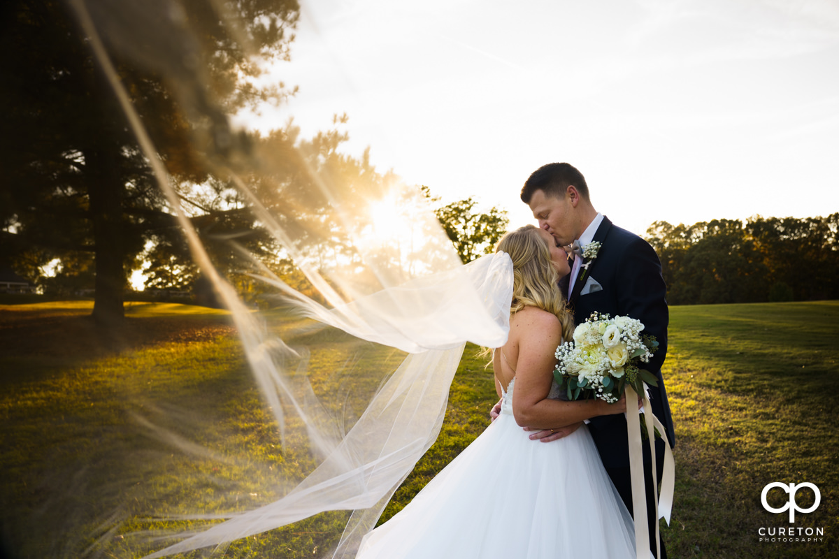 Groom kissing his bride on the forehead as her veil blows in the wind.