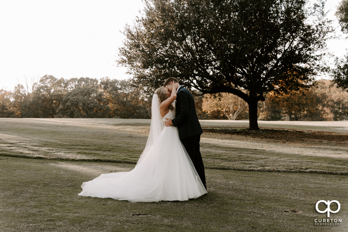 Bride and groom kissing on the golf course.