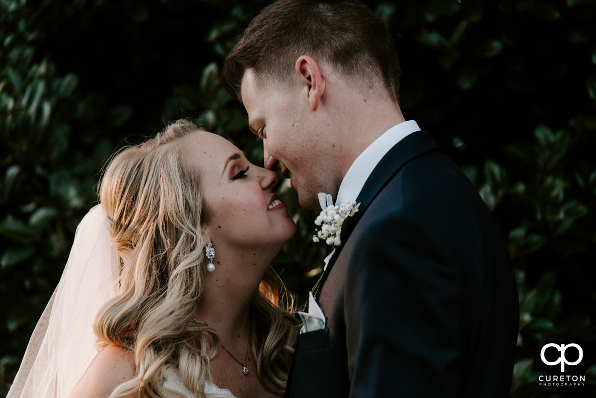 Bride and groom giving each other Eskimo kisses on their wedding day at Spartanburg Country Club.