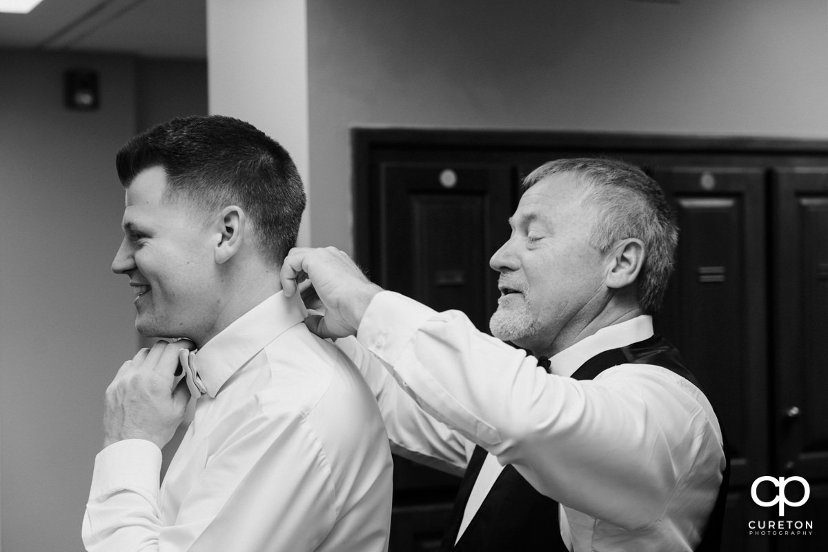Groom's father helping him with his tie.