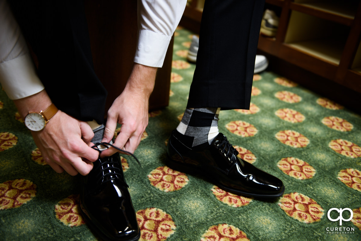 Groom tying his shoes on his wedding day.