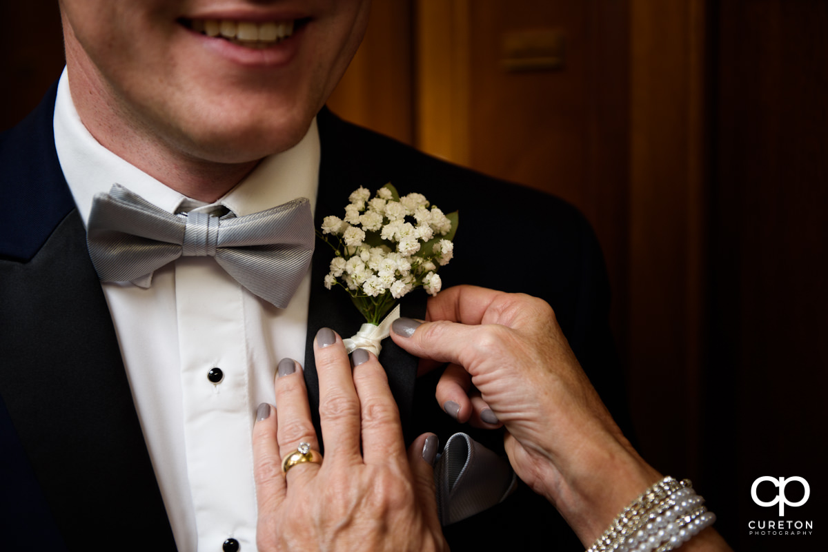 Groom's mother helping him with his boutonniere.