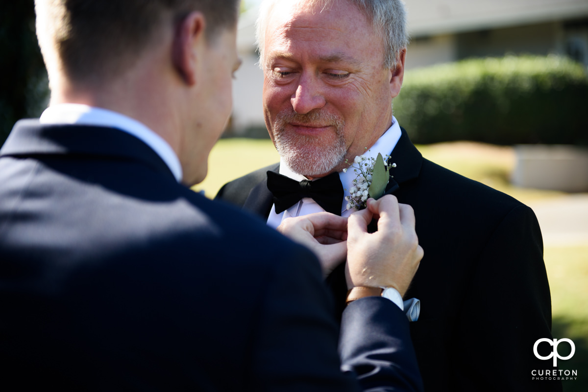Groom helping his father pin his boutonniere.