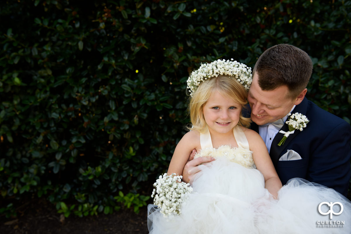Groom hugging the flower girl before the wedding.