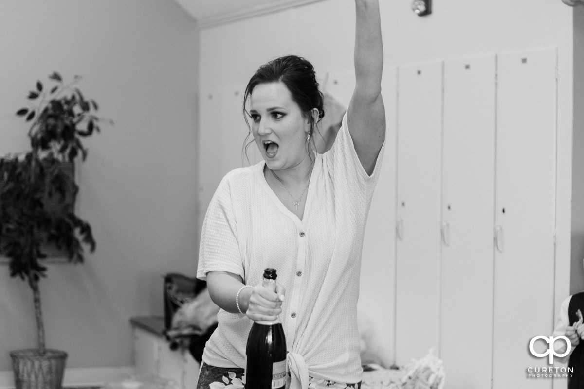 Bridesmaid popping the cork on a bottle of champagne in the bridal suite.