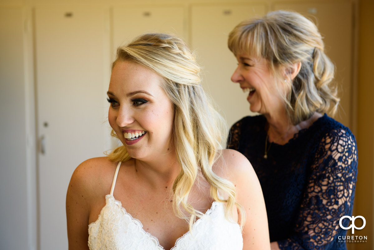 Bride laughing with her mother as she gets ready for her wedding day.