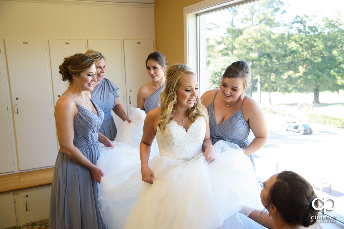 Bride laughing with her bridesmaids as they help her into her gown.