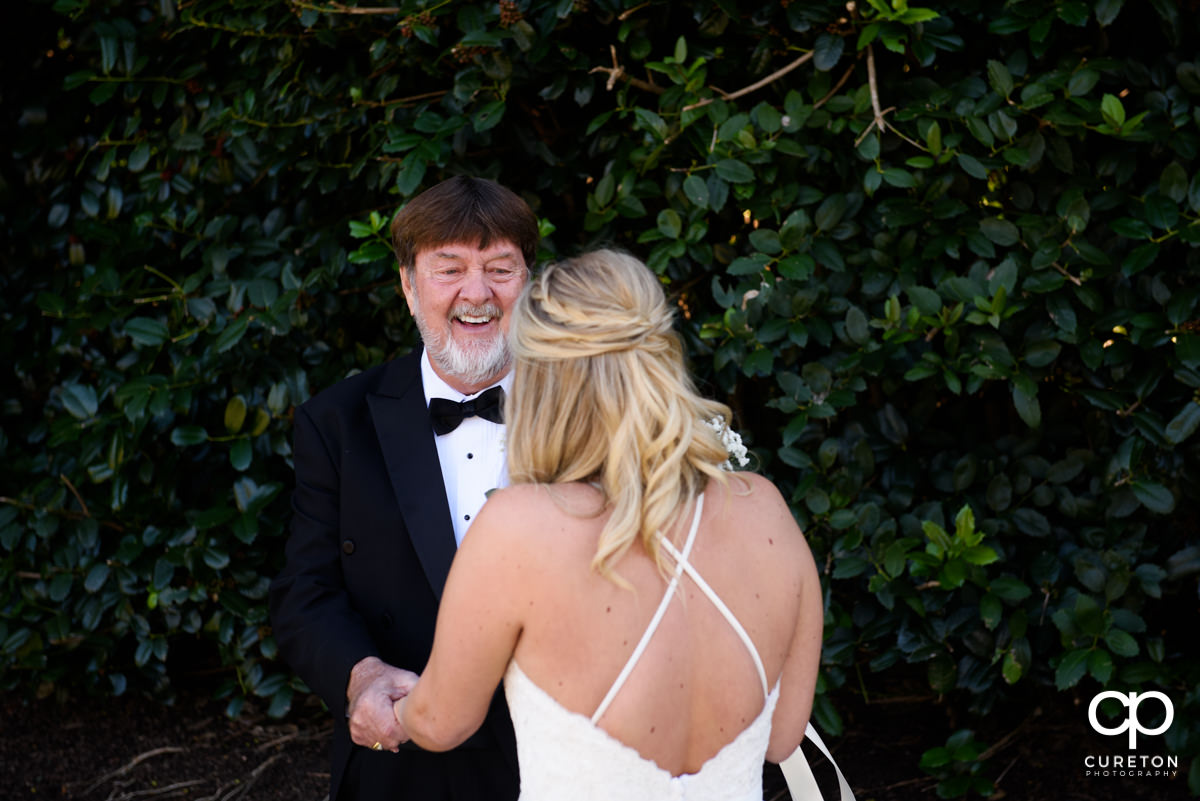 Bride's father with a huge smile on his face when he sees his daughter in her dress on the wedding day.