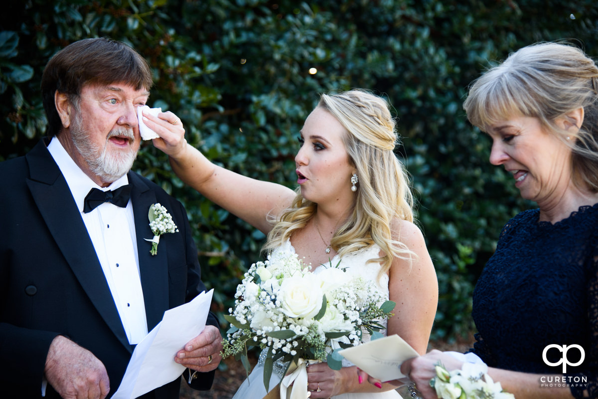 Bride wiping tears from her father's eyes as he sees her for the first time in her dress on her wedding day.