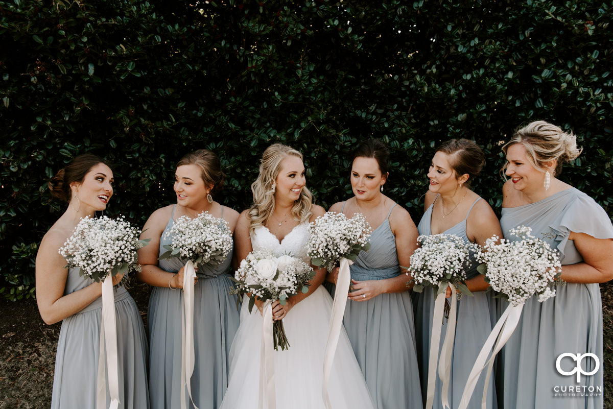 Bride laughing with her bridesmaids before the ceremony.