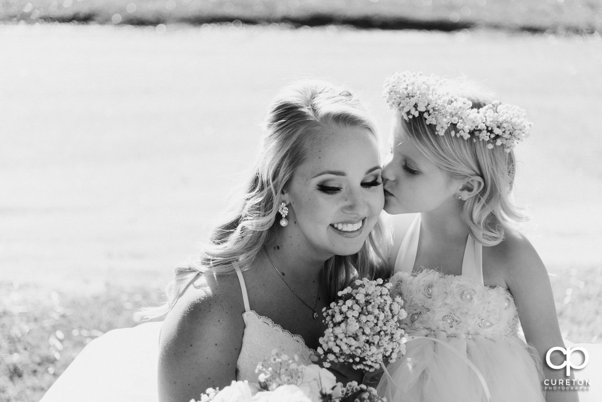 Flower girl kissing the bride on the cheek.