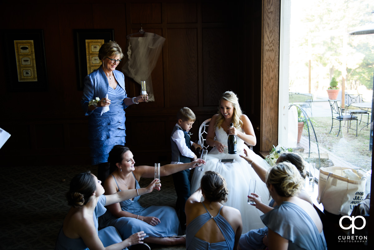 Bride sharing Champagne with her bridesmaids before she walks down the aisle.