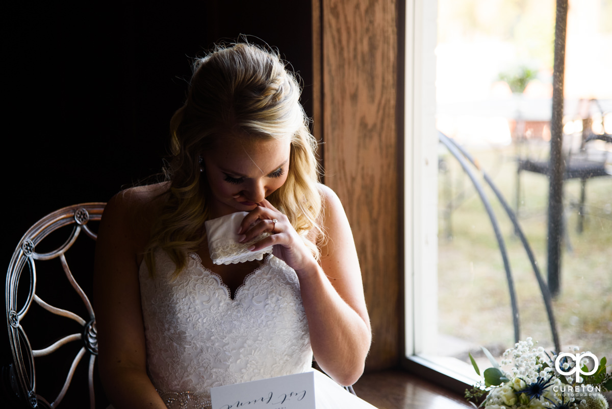 Bride tears up as she reads a letter from her husband.