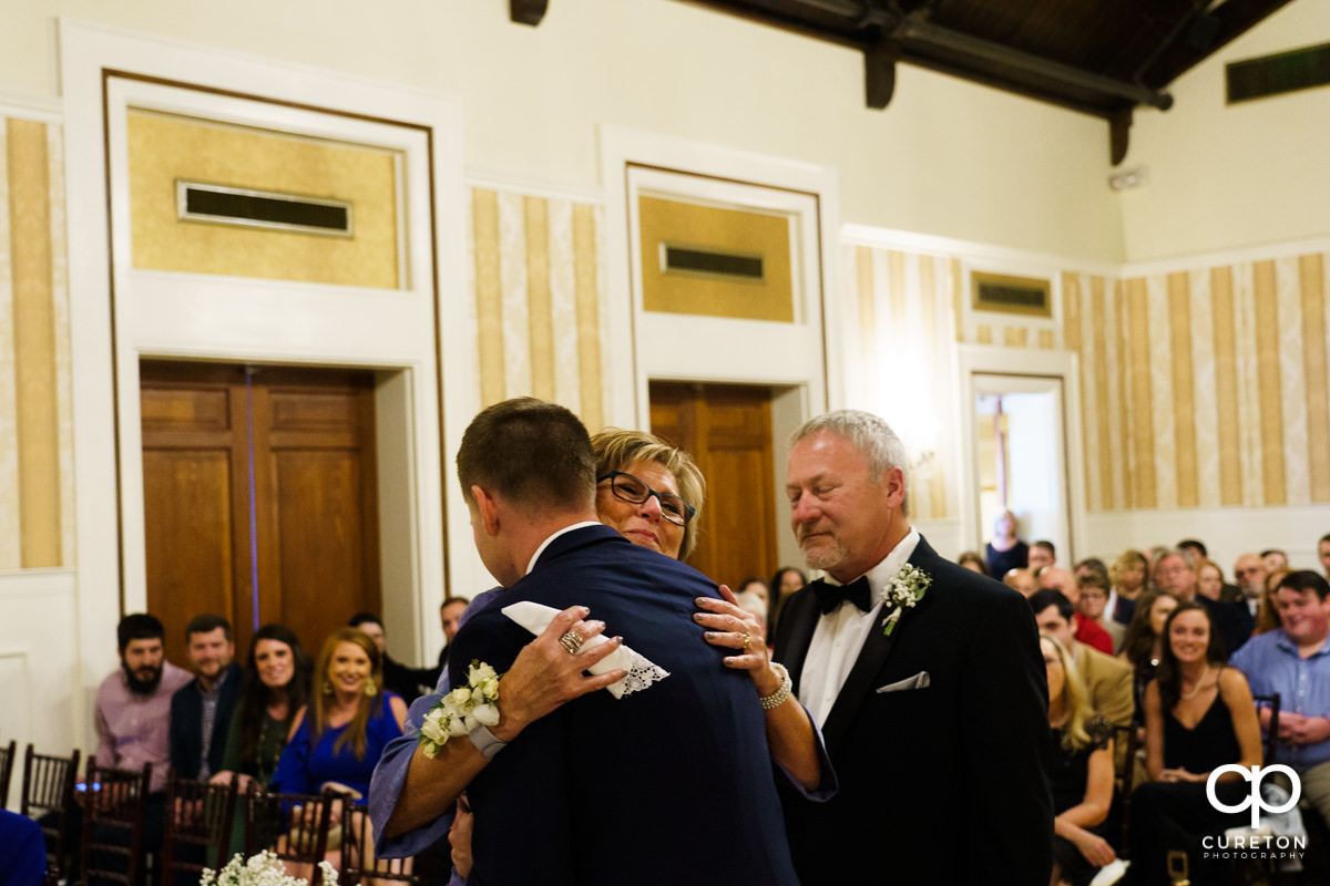 Mother of the groom of hugs her son as he walks her down the aisle.