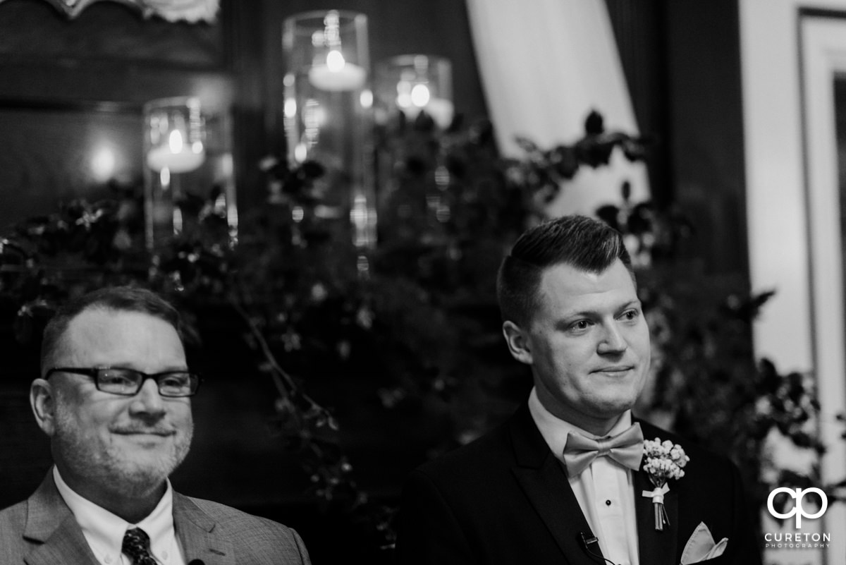 Groom with tears in his eyes as he sees his bride walking down the aisle.