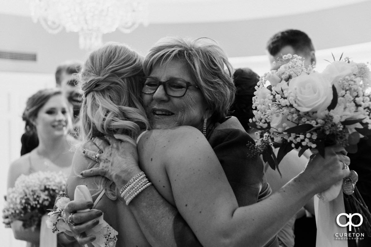 Groom's mother hugging his bride.