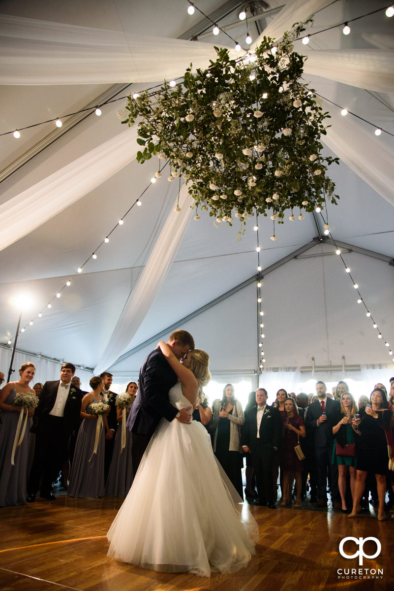 Epic first dance underneath a hanging floral installation at the Spartanburg Country Club wedding reception.