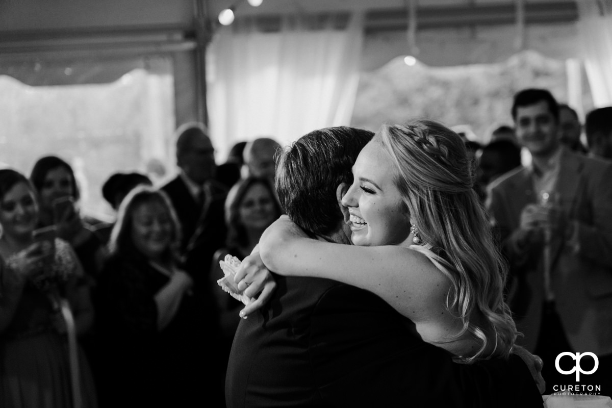 Bride hugging her father on the dance floor at the wedding reception.