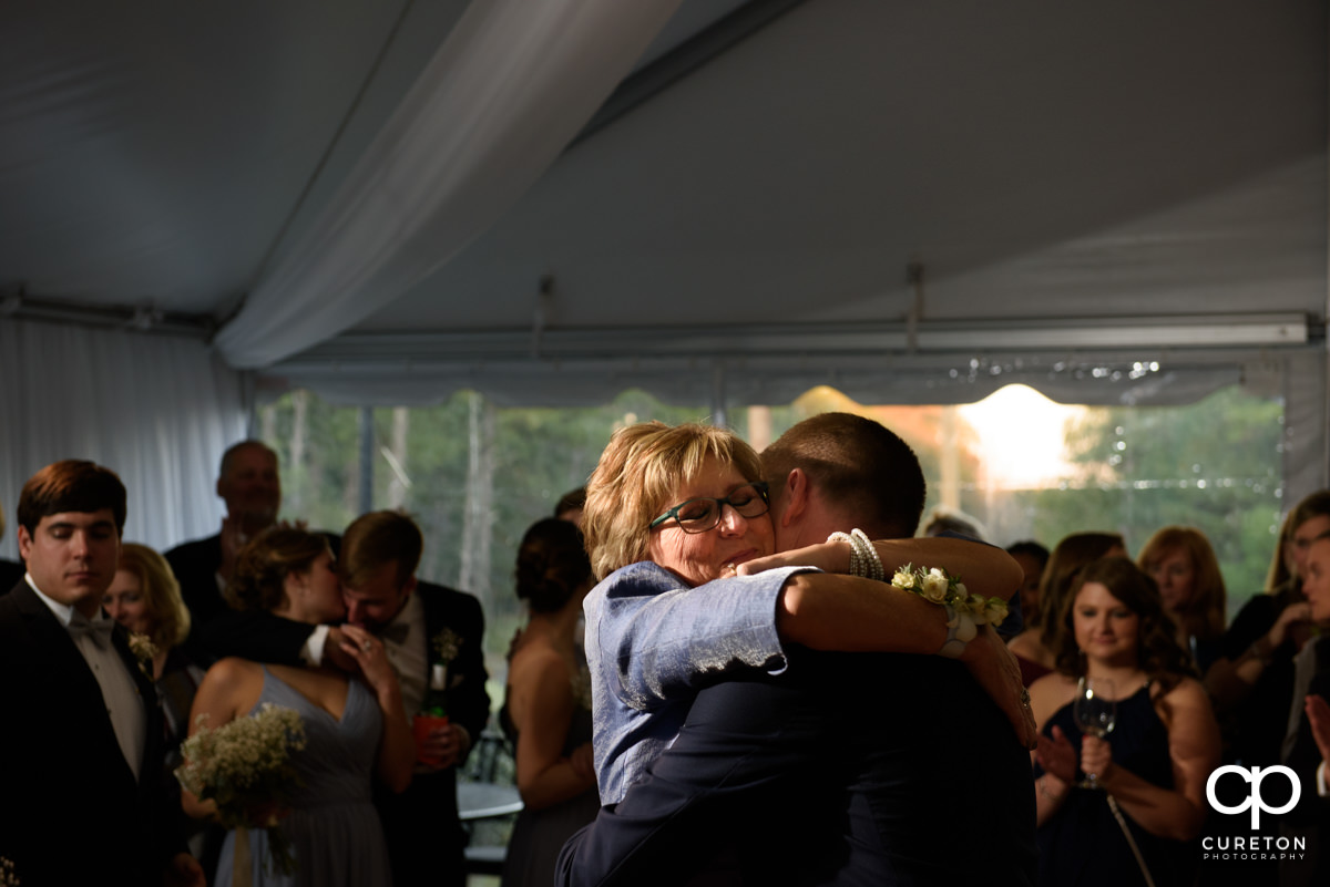 Groom's mom hugging him on the dance floor.