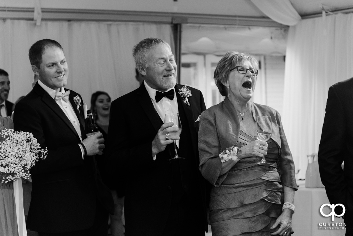 Wedding guests laughing during a speech.