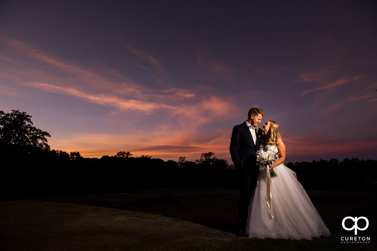 Bride and groom smiling at sunset at Spartanburg Country Club.