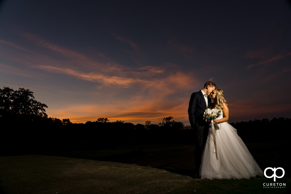 Bride and groom dancing on the golf course at Spartanburg Country Club at sunset during their wedding reception.