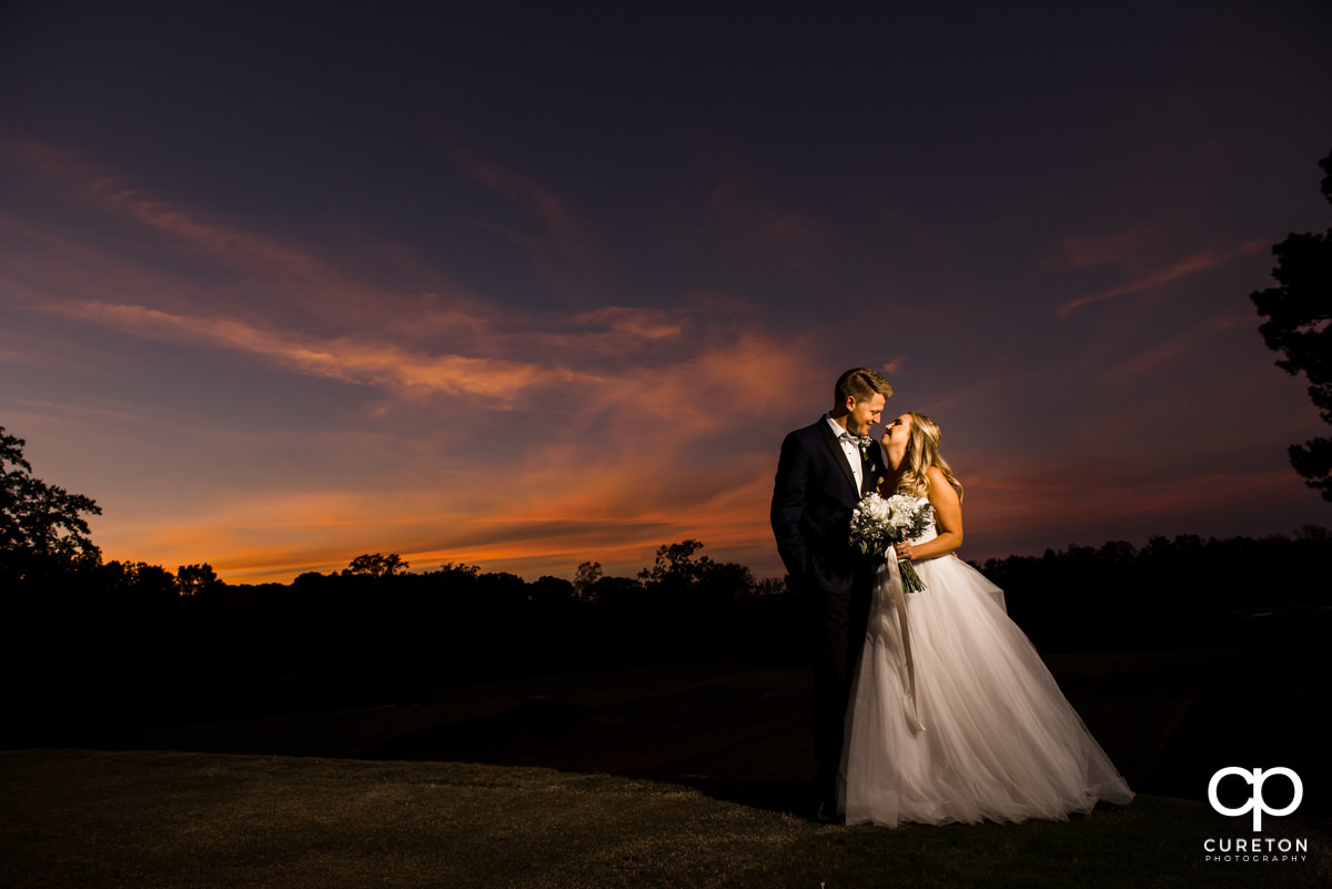 Bride and groom posing underneath an amazing sunset in Spartanburg.