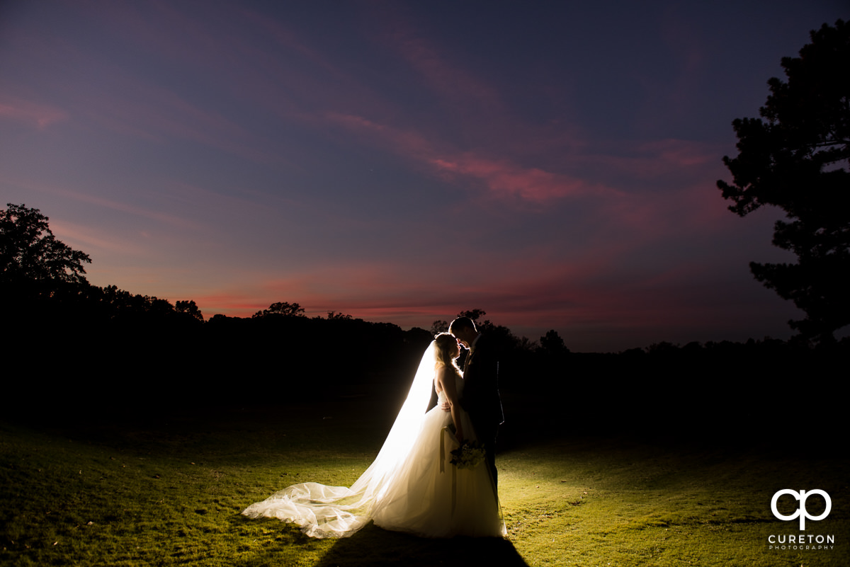 Epic back lit photo of a bride and groom on the golf course at sunset.