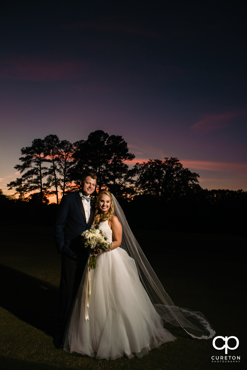 Bride and groom in front of a purple sky on their wedding day.
