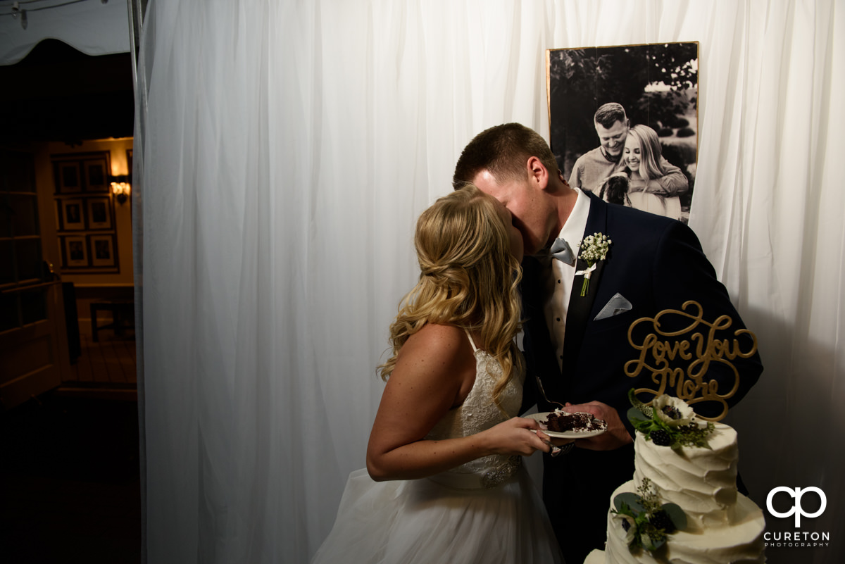 Bride and groom kissing while cutting the cake.