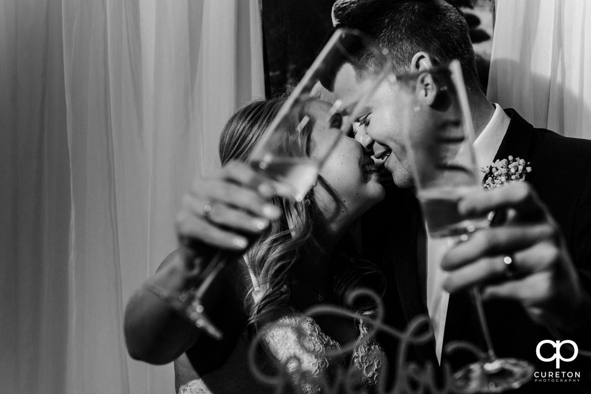 Bride and groom nuzzling with each other behind champagne flutes.