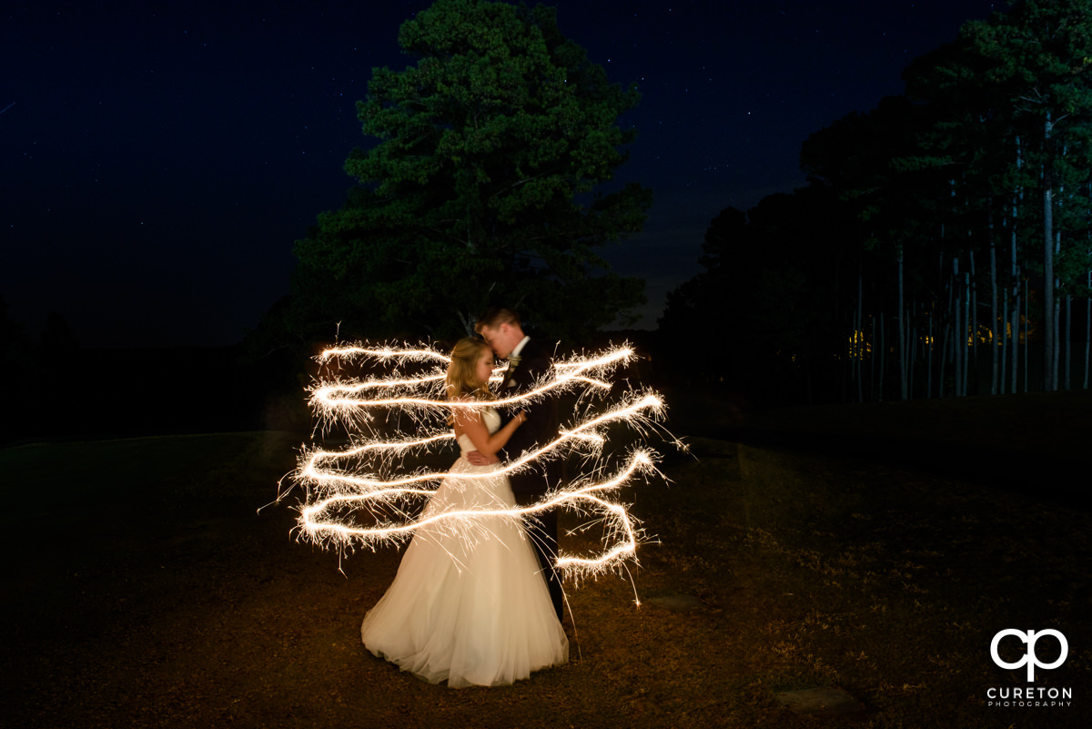 Creative photo of the bride and groom with sparklers.