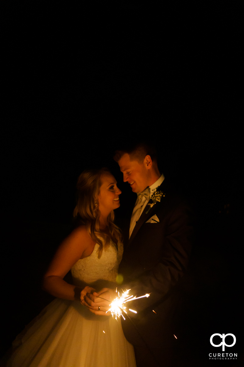 Bride and groom holding a sparkler.