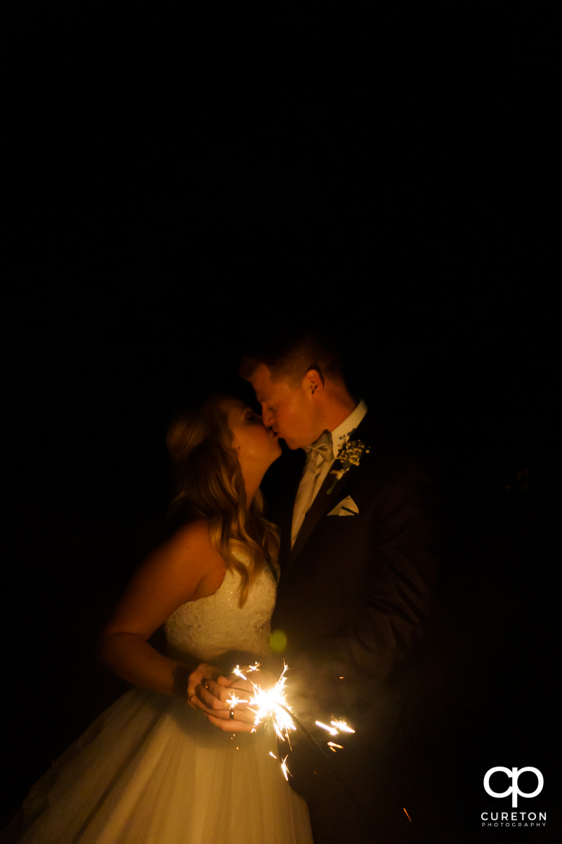 Bride and groom holding a sparkler and kissing.