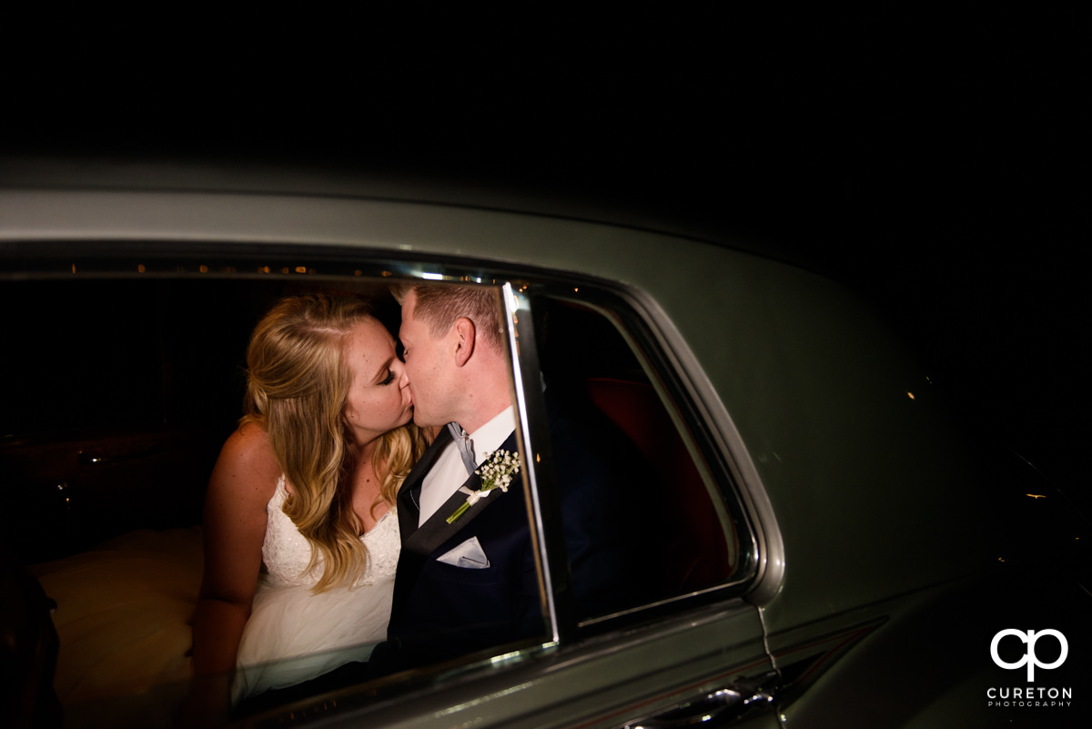 Bride and groom kissing in the getaway car.