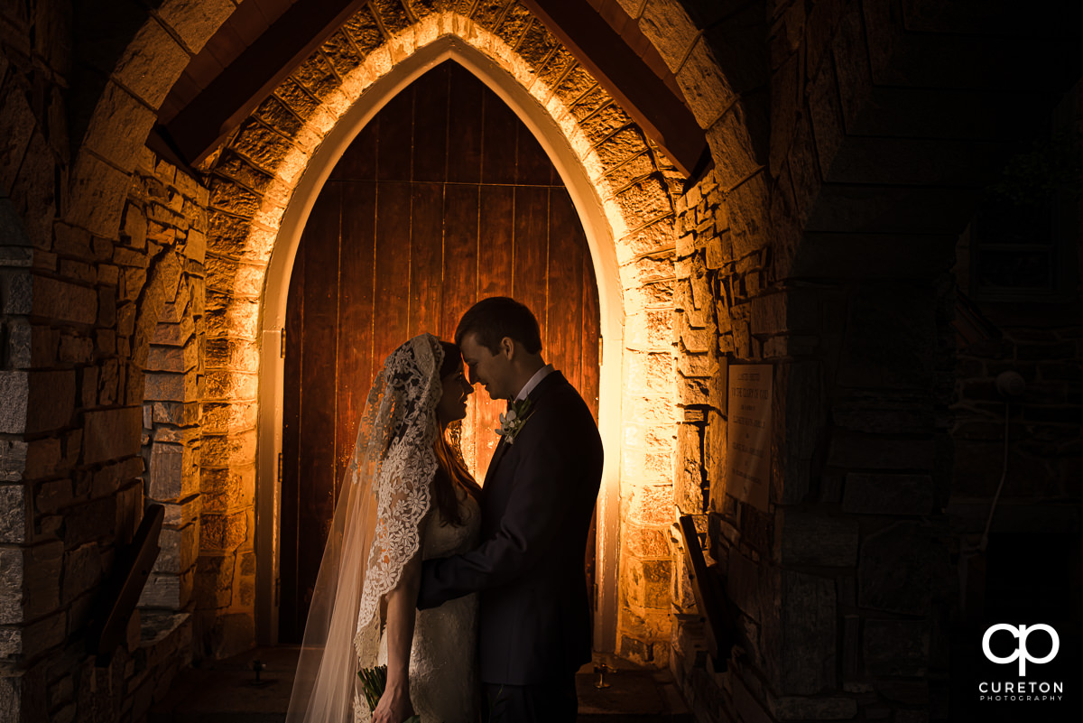 Bride and groom standing in a backlit arched doorway at the church of the advent after their Spartanburg wedding.