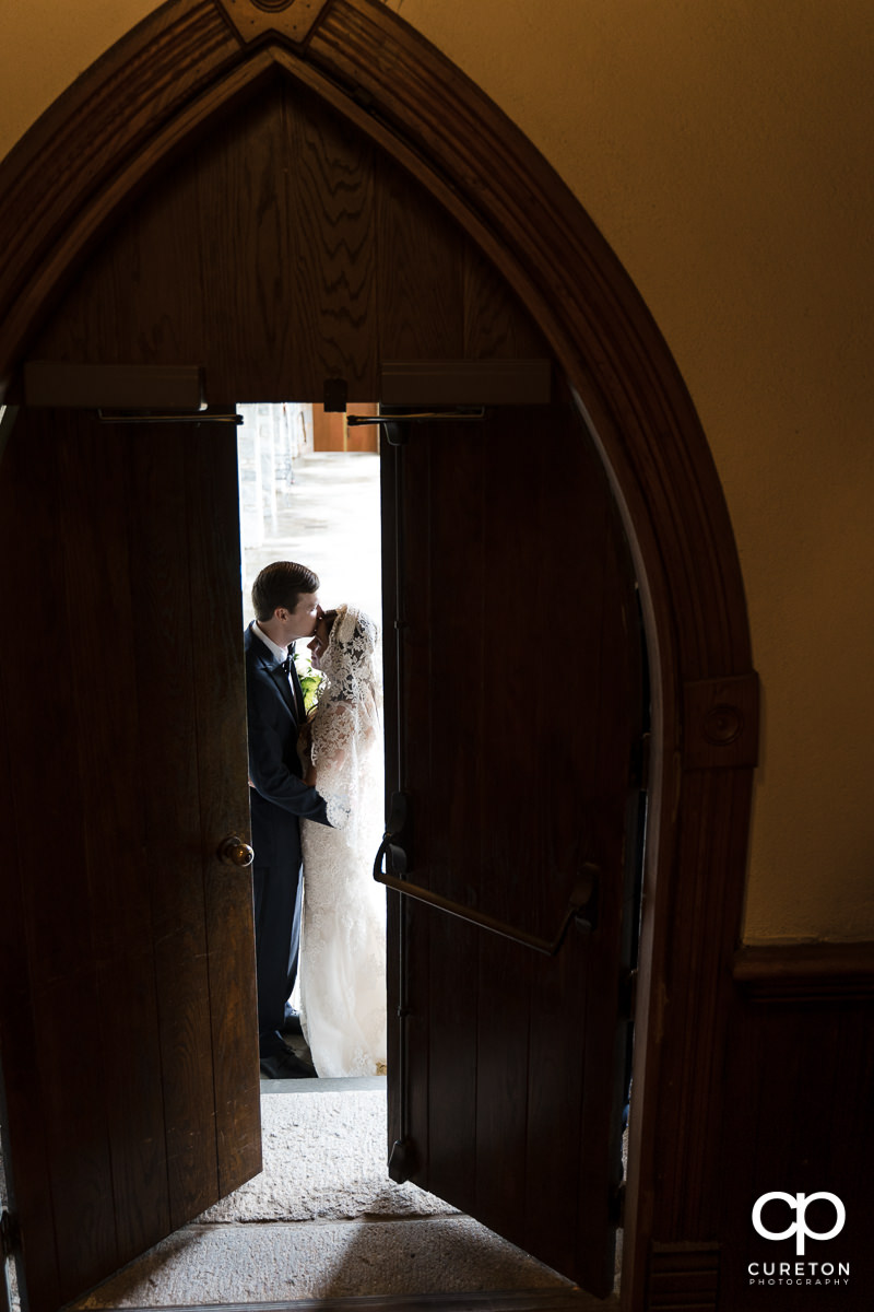 Bride and groom kissing behind opening doors at their wedding in Spartanburg.