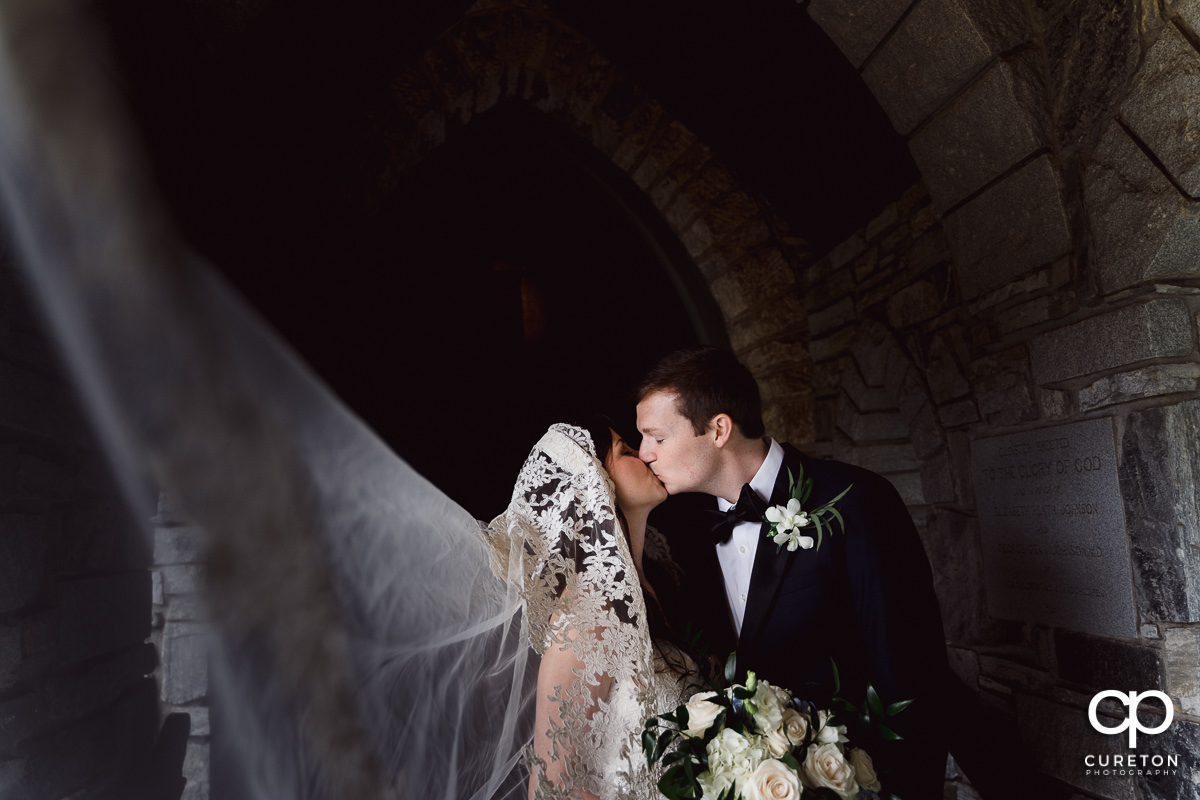 Bride and groom kissing outside of an old church while her long veil blows into the wind.