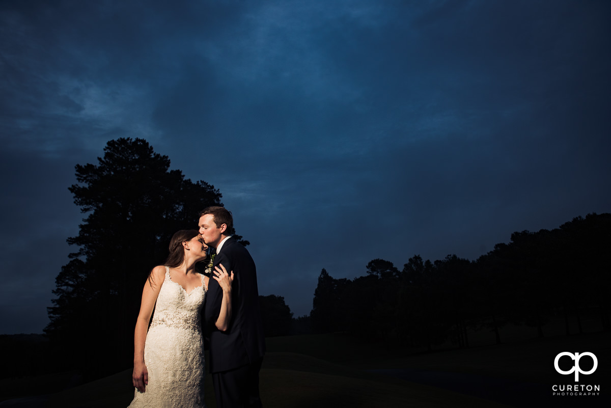 Groom kissing his bride on the forehead at sunset on the golf course at their wedding reception at Spartanburg Country Club.