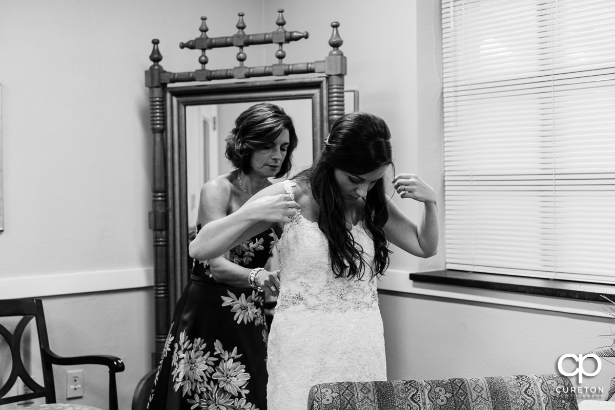 Bride being helped into her dress by her mother.