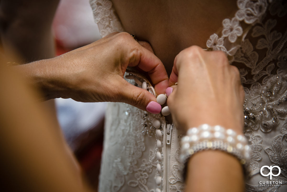 Bride's mom buttoning her dress.