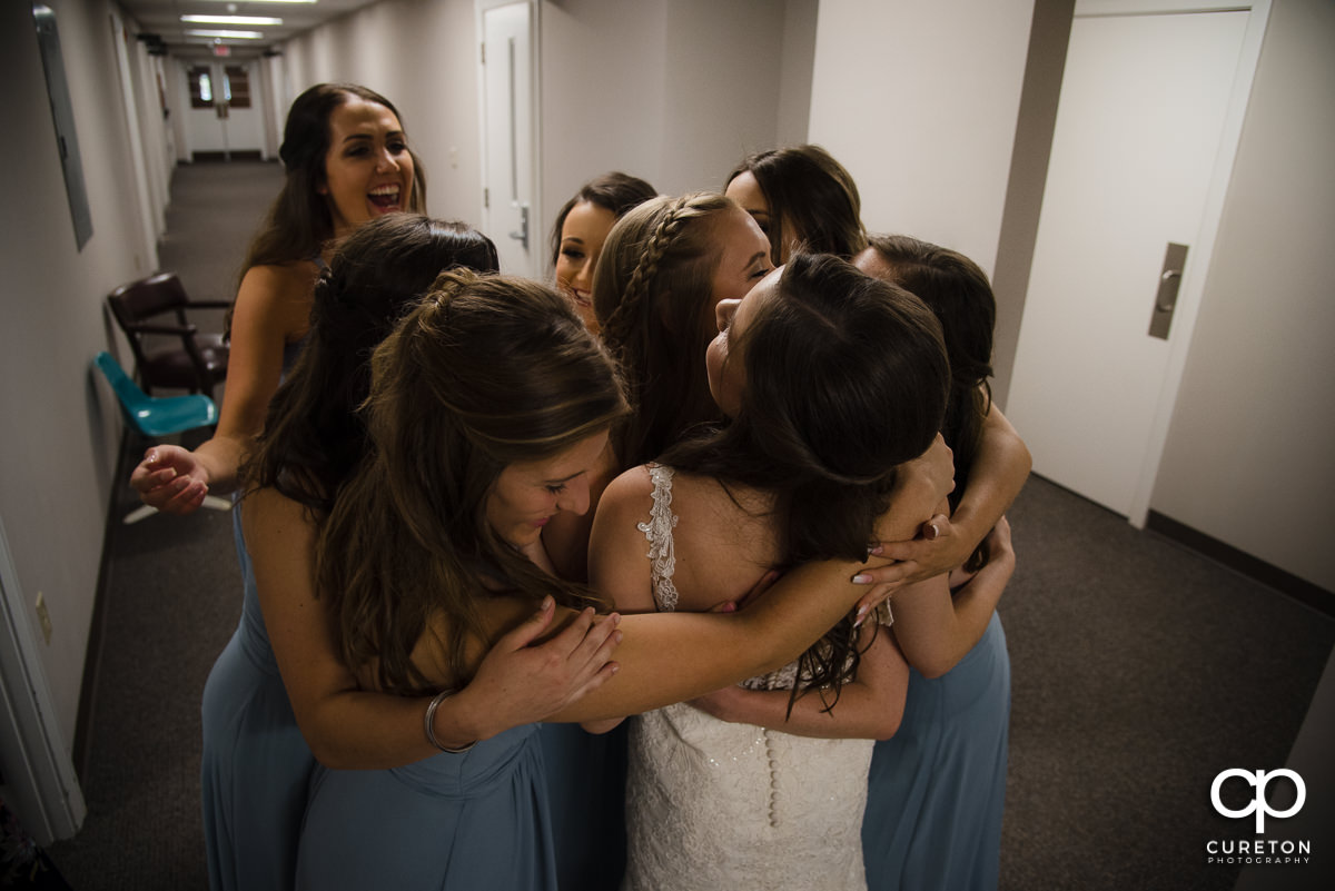 Bride being hugged by her bridesmaids.