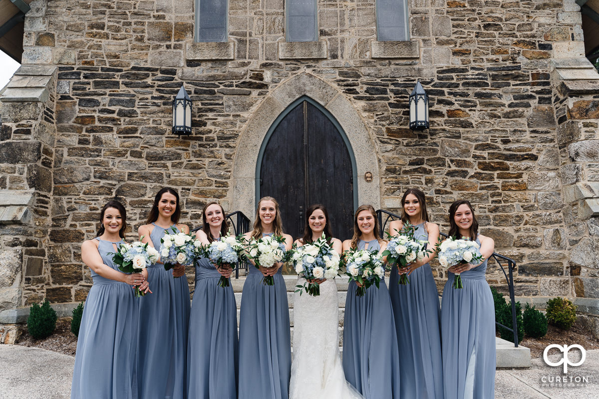 Bride and bridesmaids holding their flowers out.