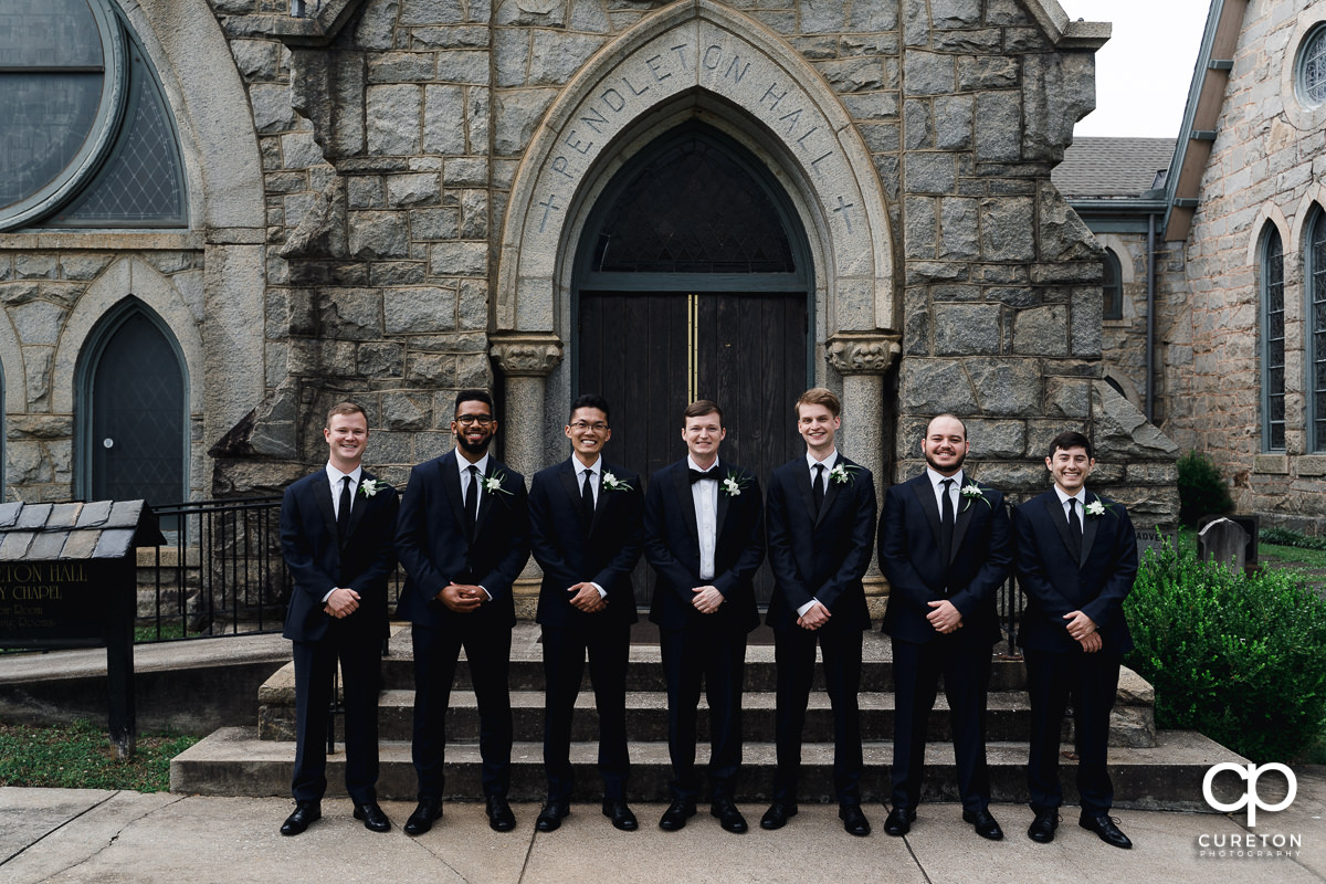 Groom and groomsmen standing outside of an antique church in Spartanburg.