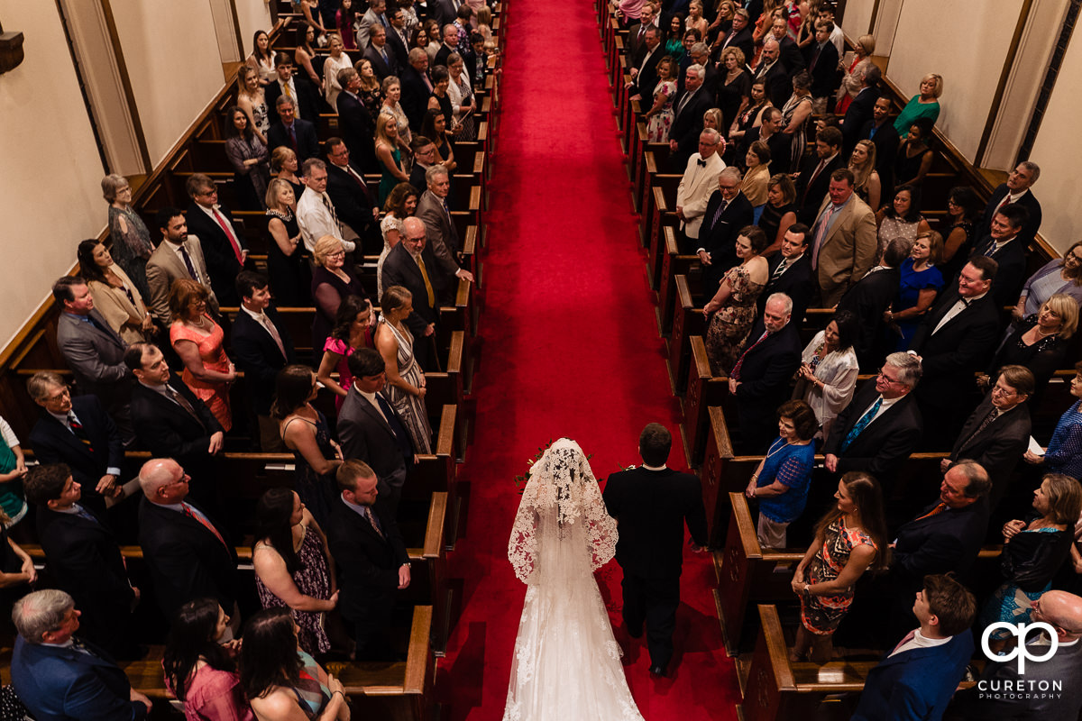 Bride and her father walking down the red aisle from above at her Spartanburg wedding.