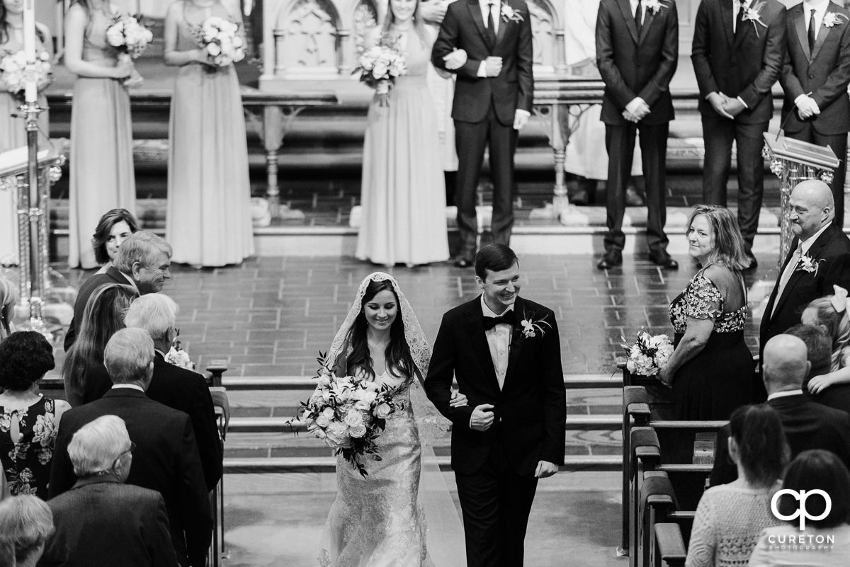 Bride and groom smiling as they walk back down the aisle after the wedding ceremony.