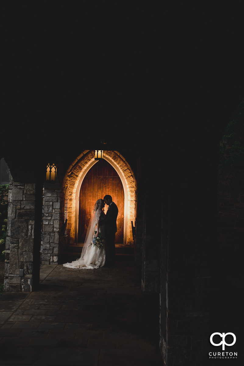 Epic photo of a bride and groom in an antique church archway in Spartanburg.