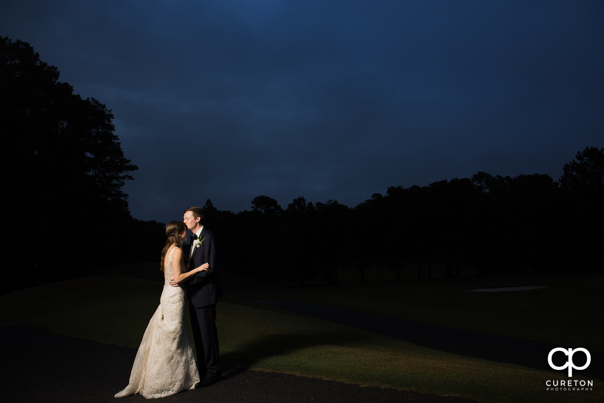 Groom kissing his bride on the forehead at twilight on the golf course at the wedding reception at Spartanburg Country Club.